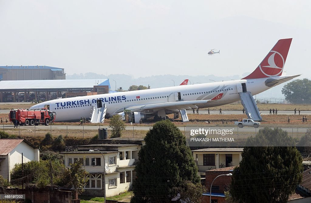 Rescue workers check the area around a Turkish Airlines plane after it slid off the tarmac at Kathmandu's international airport on March 4, 2015. The plane with 224 passengers onboard made the emergency landing at the airport after missing the runway and skidding on to nearby grassland, aviation officials said.