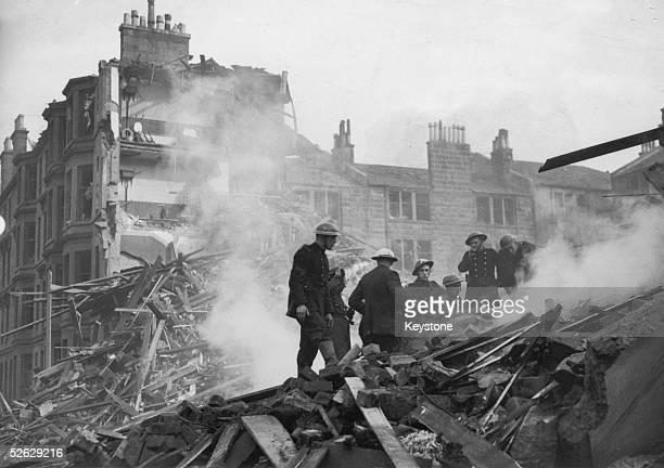 Rescue workers clamber over the smoulder wreckage of a building in Clydeside trying to find people trapped in the ruins after the bombing raid of the...