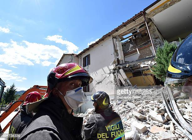 Rescue workers clear debris while searching for victims in damaged buildings on August 24 2016 in Accumoli Italy Central Italy was struck by a...
