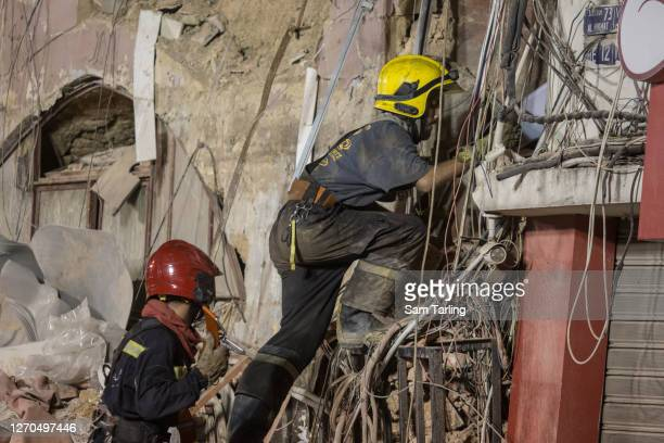 Rescue workers climb into a destroyed building to find a potential survivor 30 days after the explosion in Beirut port, on September 3, 2020 in...