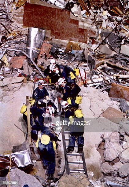 Rescue workers climb over debris 20 April 1995 at the Albert P Murrah Federal Building in Oklahoma City few hours after a fuelandfertilizer truck...