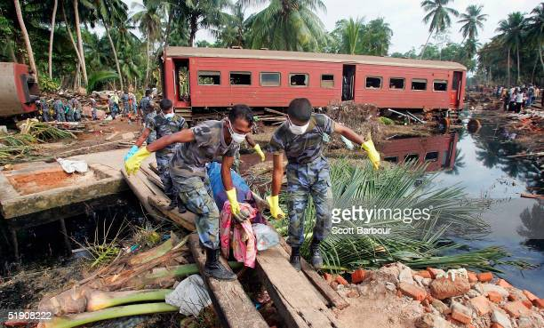 Rescue workers continue to remove bodies from the scene of a train crash caused by the tsunami which left almost all of its 1200 passengers dead...