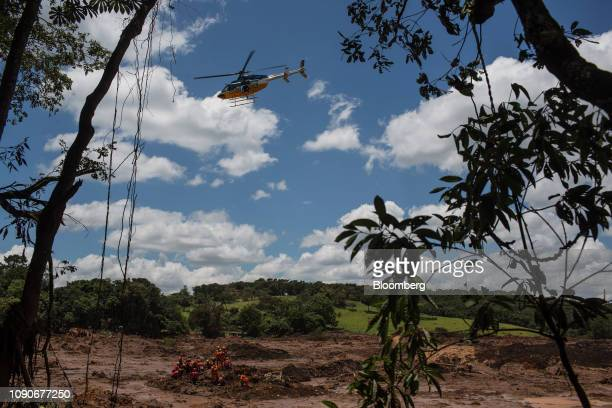 Rescue workers coordinate with a helicopter while attempting to remove a body from the debris of a bus after a Vale SA dam burst in Brumadinho, Minas...