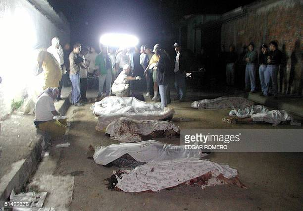 Rescue workers count bodies lined up in a street of the Las Colinas community near Santa Tecla El Salvador 13 January 2001 following a massive...