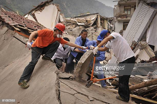 Rescue workers dig for people who are still alive in destroyed houses in the town of Beichuan on May 15 2008 which has been cut off after a powerful...