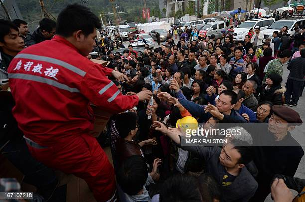 Rescue workers distribute food after a magnitude 70 earthquake hit Lushan Sichuan Province on April 21 2013 At least 160 people were killed and 6700...