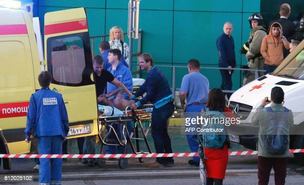 Rescue workers evacuate a man from the Rio shopping mall in Moscow on July 10 2017 Ten people poisoned by smoke were hospitalised after a fire broke...