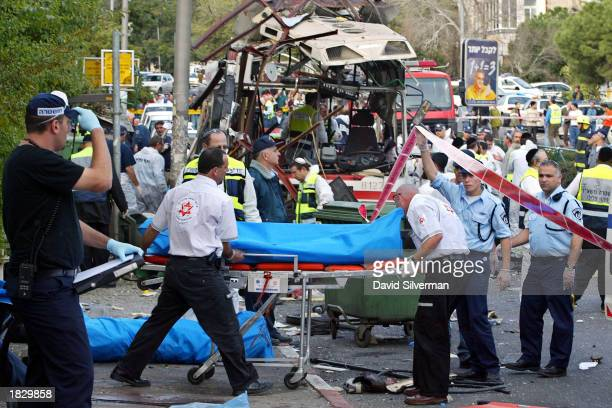 Rescue workers evacuate a victim's body from the scene of a Palestinian suicide bombing on an Israeli bus March 5 2003 in the northern Israeli city...