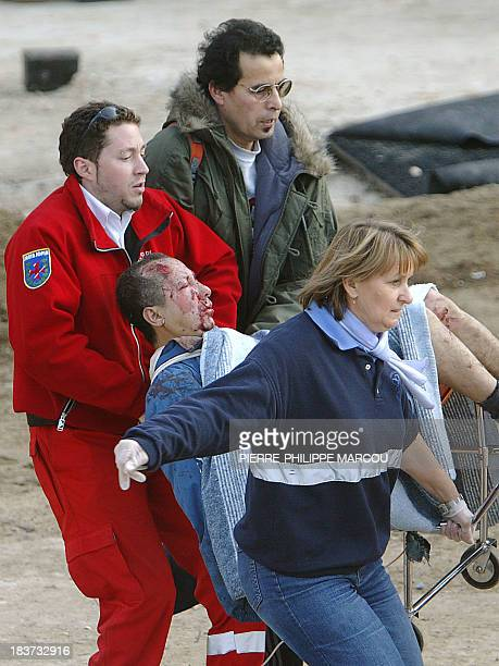 Rescue workers evacuate an injured person after a train exploded at the Atocha train station in Madrid 11 March 2004 At least 173 people were killed...