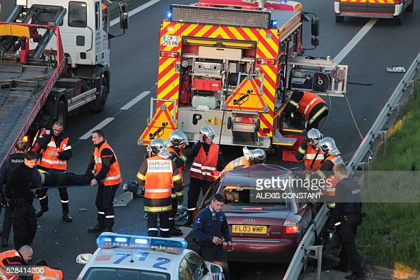 Rescue workers evacuate an injured person as police inspect the site of an accident on the A16 motorway in Coudekerque near Dunkerque northern France...
