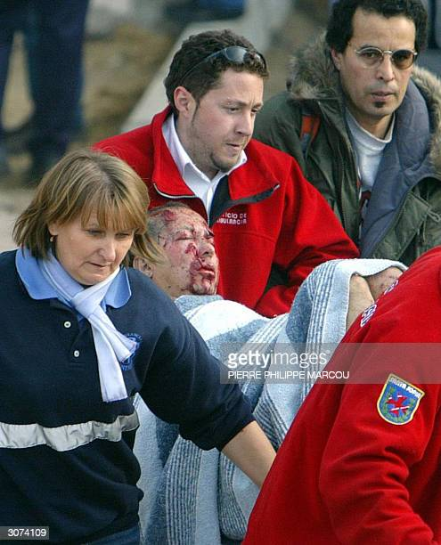 Rescue workers evacuate an injured person at the Atocha railway station in Madrid 11 March 2004 At least 72 people were killed and many hundreds...
