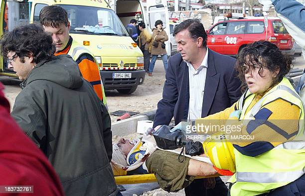 Rescue workers evacuate an injured person in front of a destroyed train at the Atocha railway station in Madrid 11 March 2004 At least 72 people were...