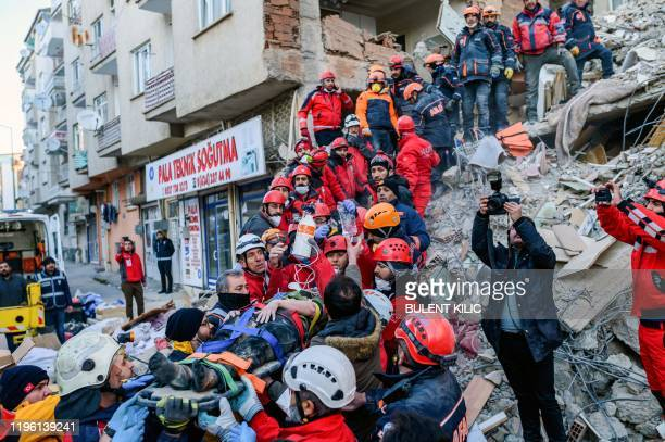 TOPSHOT Rescue workers evacuate an injured woman from the rubble of a building after an earthquake in Elazig eastern Turkey on January 25 2020 Rescue...