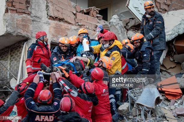 Rescue workers evacuate an injured woman from the rubble of a building after an earthquake in Elazig eastern Turkey on January 25 2020 Rescue workers...