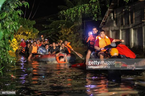 Rescue workers evacuate floodaffected residents in Davao on the southern Philippine island of Mindanao early on December 23 after Tropical Storm...