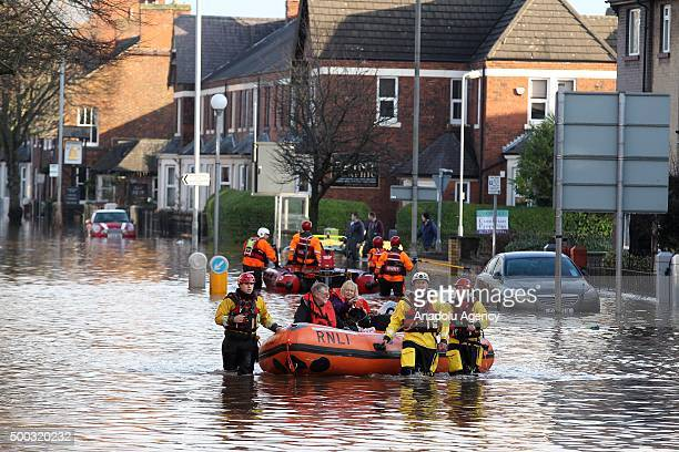 Rescue workers evacuate residents from their flooded homes after the nearby river Eden burst it's banks over the weekend in Carlisle Cumbria in north...