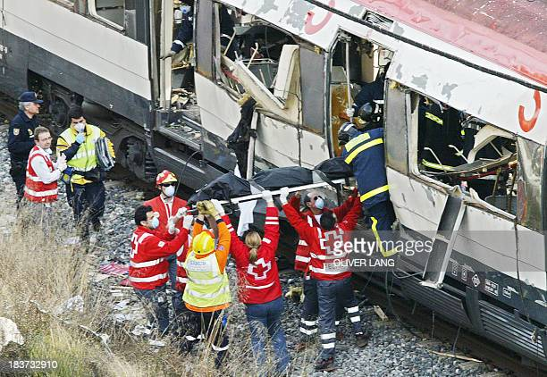 Rescue workers evacuate the body of a victim after a train exploded near the Atocha train station in Madrid 11 March 2004 At least 186 people were...