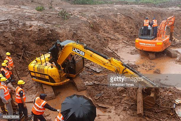 Rescue workers from NDRF continue their efforts to dig in swirling sludge to find way into dozens of submerged homes at the site of a landslide in...