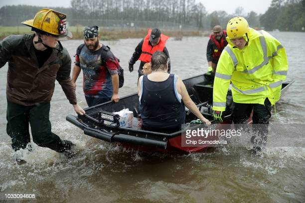 Rescue workers from Township No 7 Fire Department and volunteers from the Civilian Crisis Response Team use a boat to rescue a woman and her dog from...