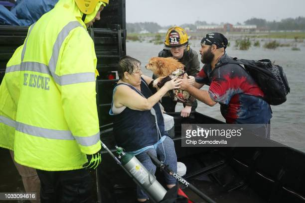 Rescue workers from Township No 7 Fire Department and volunteers from the Civilian Crisis Response Team help rescue a woman and her dog from their...