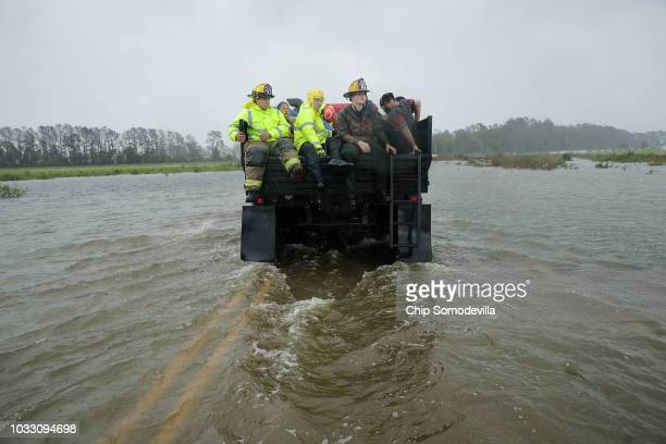 Rescue workers from Township No 7 Fire Department and volunteers from the Civilian Crisis Response Team use a truck to move people rescued from their...