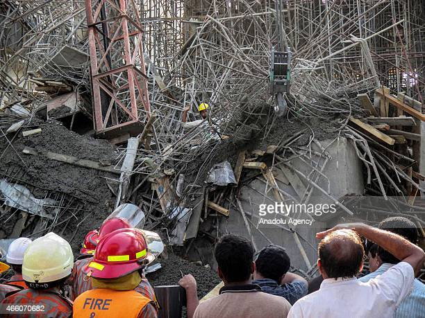 Rescue workers gather at the partlybuilt cement factory which collapsed in the port town of Mongla 200km southwest of the capital Dhaka on March 12...