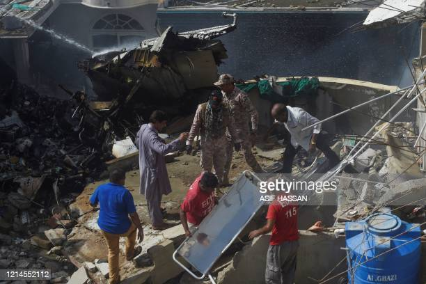 Rescue workers gather at the site after a Pakistan International Airlines flight crashed in a residential neighbourhood in Karachi on May 22 2020 A...