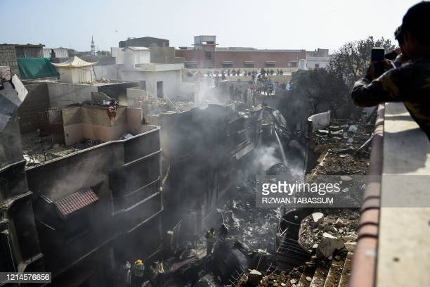 TOPSHOT Rescue workers gather at the site after a Pakistan International Airlines aircraft crashed in a residential area in Karachi on May 22 2020 A...
