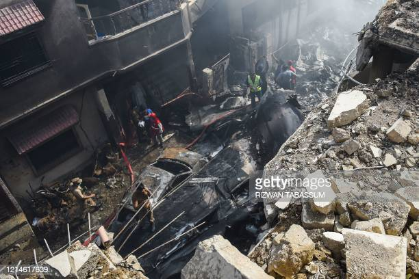 Rescue workers gather at the site after a Pakistan International Airlines aircraft crashed in a residential area in Karachi on May 22 2020 A...