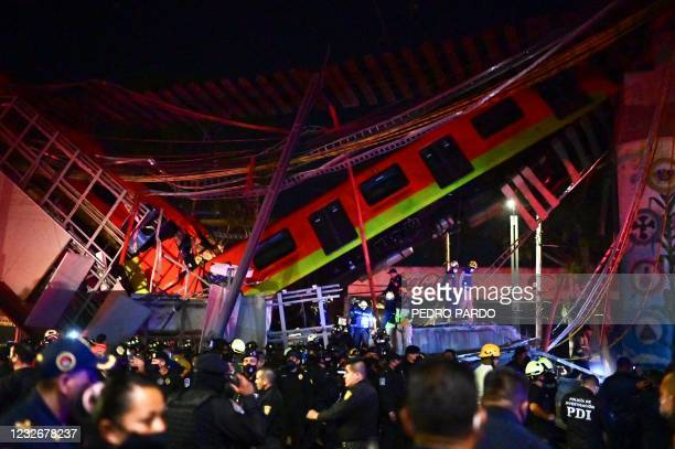 Rescue workers gather at the site of a metro train accident after an overpass for a metro partially collapsed in Mexico City on May 3, 2021. - At...