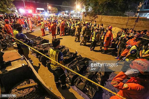 Rescue workers gather bags containing dead bodies of victims of an explosion at a night market in Davao City in southern island of Mindanao early...