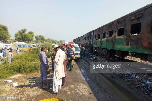 Rescue workers gather beside the burnt-out train carriages after a passenger train caught on fire near Rahim Yar Khan in Punjab province on October...