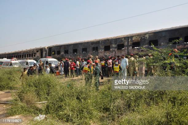 Rescue workers gather in front of the burnt-out train carriages after a passenger train caught on fire near Rahim Yar Khan in Punjab province on...