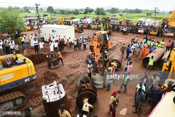 Rescue workers gather with heavy digging equipment during an operation to rescue a toddler stuck in a deep well near Manapparai town in...
