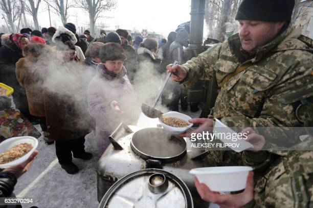 TOPSHOT Rescue workers give food to local residents in the Ukrainian town of Avdiivka on February 1 2017 as government forces and Russianbacked...