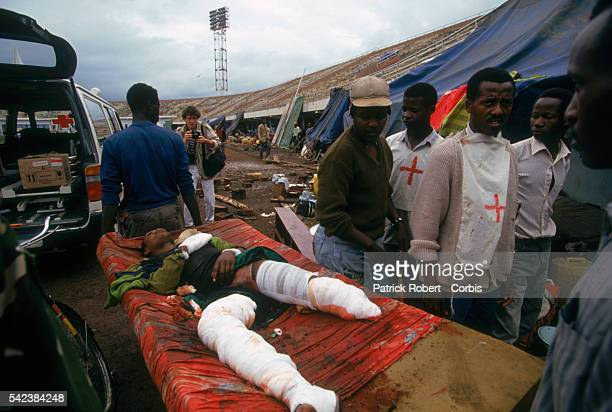 Rescue workers help the wounded after the Amahoro Stadium was bombed by the army during the civil war in Rwanda In the background french...