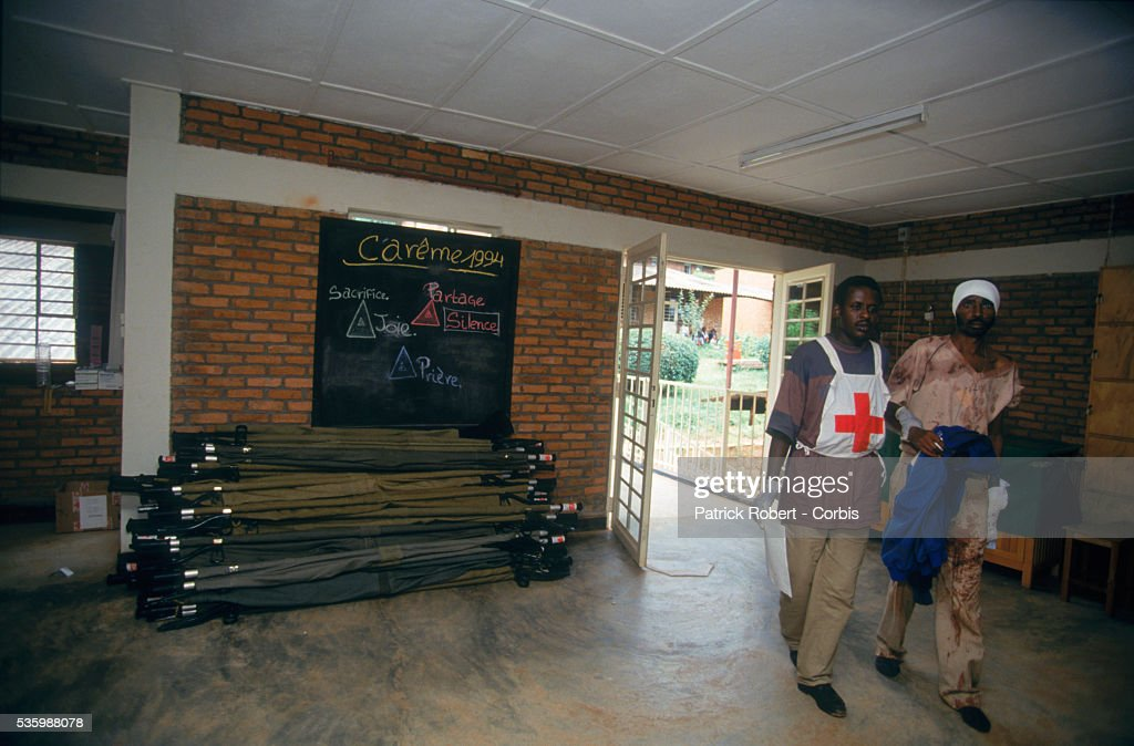 Rescue workers help the wounded at a Red Cross hospital after the Amahoro Stadium was bombed by the army during the civil war in Rwanda.