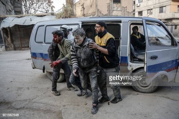 Rescue workers help wounded men to take them to the hospital after Assad Regime carried out an airstrike over Sakba town of Eastern Goutha region...