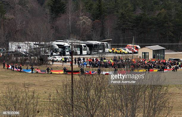 Rescue workers hold up flags representing the nationalities of those killed onboard Germanwings flight 4U9525 as friends and relatives arrive at a...
