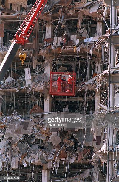 Rescue workers in a basket survey damages 20 April 1995 to the Albert P Murrah Federal Building in Oklahoma City one day after a fuelandfertilizer...