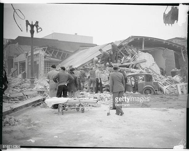 Rescue workers inspect the ruins of a drug store and apartment house at Compton Avenue and Tamarina Street in Compton Cal after the series of...