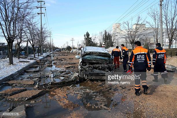 Rescue workers inspect the scene of a natural gas pipeline blast which injured 2 people and damaged cars parked on nearby streets in southern Turkish...