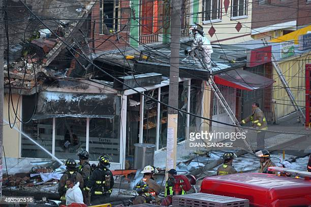 Rescue workers inspect the site of the aircrash of BEECHCRAFT60 plane in Engativa neighborhood in Bogota on October 18 2015 A small plane crashed...