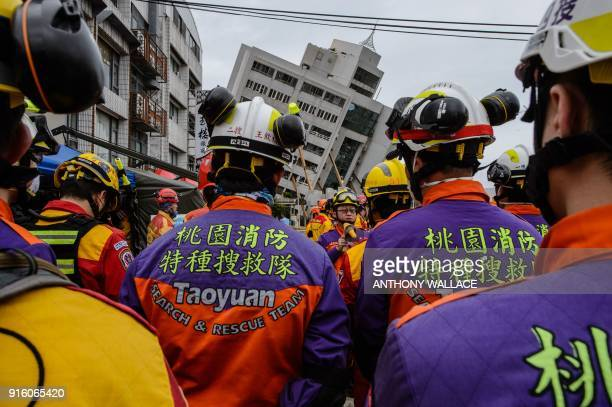 Rescue workers lineup for a briefing outside the Yun Tsui building which is leaning at a precarious angle before the recovery of the bodies of a Hong...