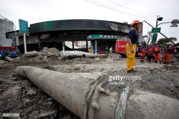Rescue workers look at the remains of a damaged road after several gas explosions took place in southern Kaohsiung on August 1 2014 in Kaohsiung...