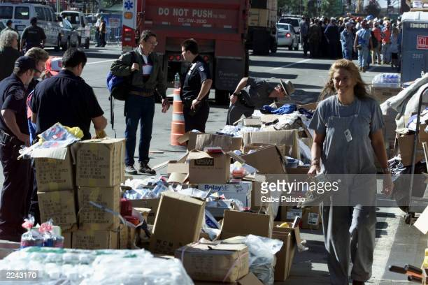 Rescue workers look for needed supplies in the collection of donated goods including food water boots socks and gloves on the West Side Highway near...