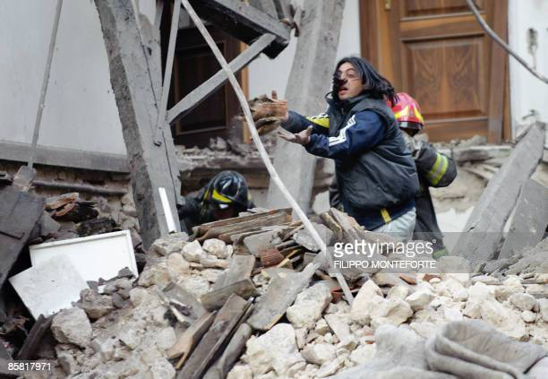 Rescue workers look for survivors in the ruins of a collapsed house on April 6, 2009 in the center of the Abruzzo capital L'Aquila, the epicenter of...