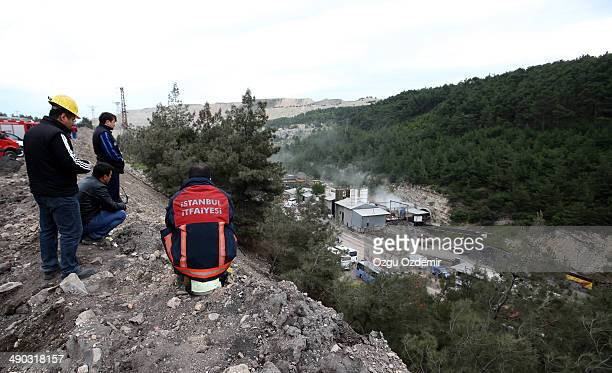 Rescue workers look on as smoke billows from the coal mine on May 14, 2014 in Soma, Manisa, Turkey. An explosion and fire in the coal mine killed at...