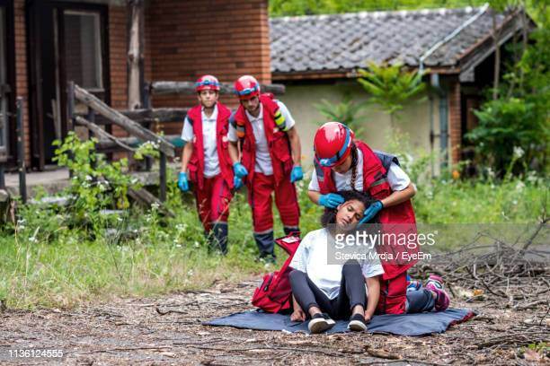 rescue workers looking at colleague examining injured woman during tornado - rescue worker stock pictures, royalty-free photos & images