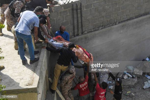 Rescue workers move a body from the site after a Pakistan International Airlines aircraft after crashed at a residential area in Karachi on May 22...